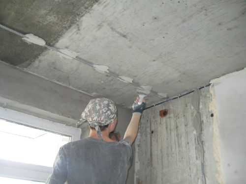 Выставляем маяк на потолок и убираем лишний раствор