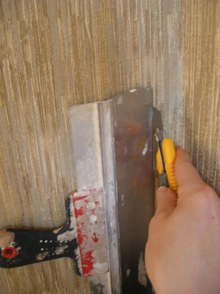 Прикладываем шпатель в место нахлеста обоев и прорезаем обои по шпателю канцелярским ножем