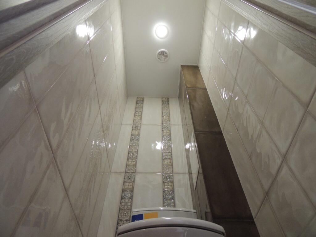Коричневая плитка на  коробе и светлая плитка по стенам в туалете