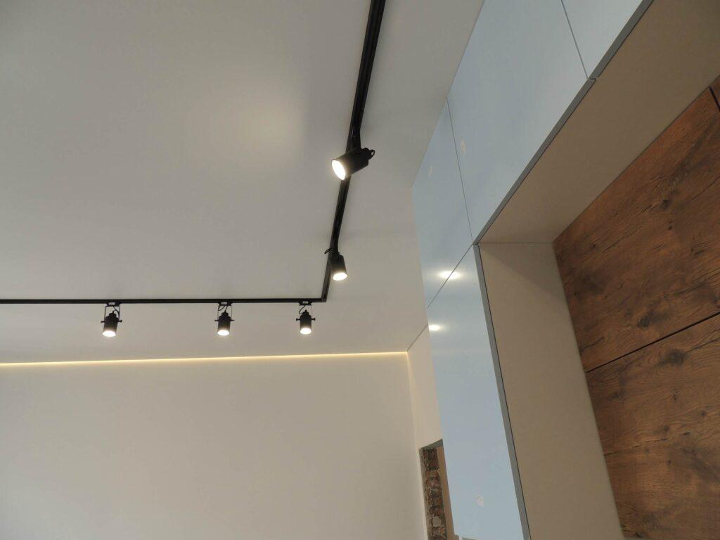 Чёрный трековый светильник на белом натяжном потолке